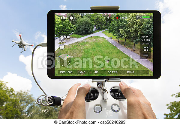 Cropped image of hands controlling drone filming park seen on digital tablet