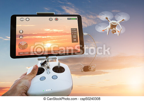 Cropped image of hand controlling drone filming orange sky seen on digital tablet during sunset
