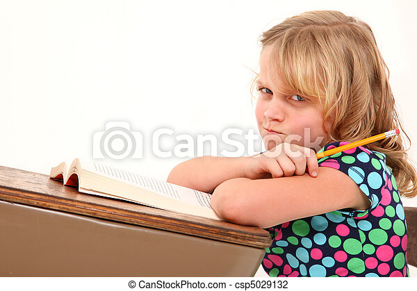 Adorable 7 year old girl making angry expression in desk over white background.