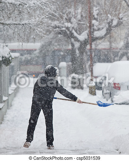 Woman shoveling snow from a sidewalk - csp5031539