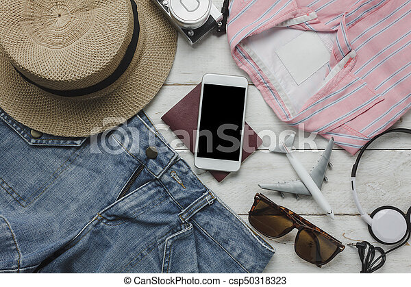 Aerial view of accessories clothing women to travel with technology background concept.Essential items for traveler or teenage and adult prepare to holiday trip.Several object on modern white wood.
