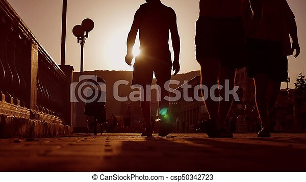 Heat people crowd. Unknown people sunset crowd silhouette walking from sea . Silhouettes of people the sun