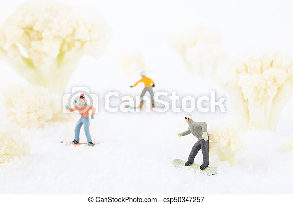 A photo of snowboarding toy people among the cauliflowers, which look like trees in snow.