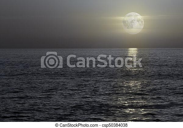 Full moon at night or dusk at sea