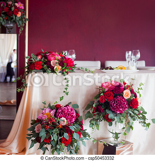 Wedding decor. decor of the newlyweds. Silk tablecloths, red flowers
