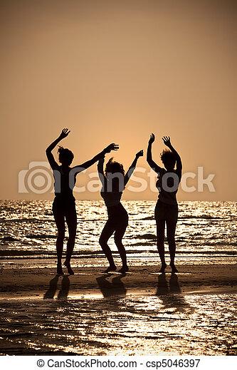 tres, joven, mujeres, bailando, en, playa, en, ocaso - csp5046397