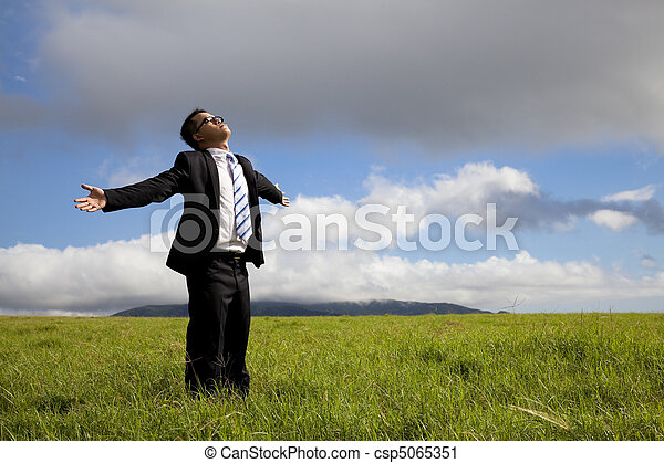 Relaxation businessman standing on the meadow - csp5065351