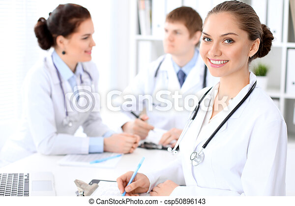 Happy female doctor and medical staff discussing something while sitting at the table. Successful team at health care and medicine concept