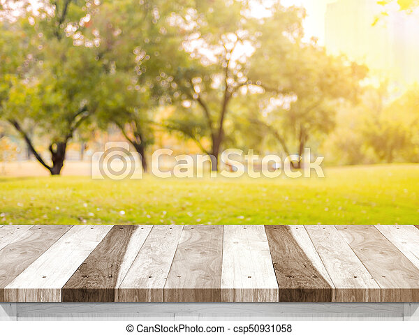 Empty old rustic wood plank table top with blur forest tree with sunlight,Autumn fall backgorund,Mock up for display or montage of product,banner for advertise on online