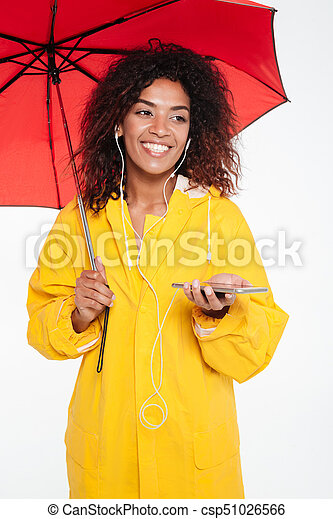 Vertical image of happy african woman in raincoat hiding under umbrella and listening music on her smartphone while looking away over white background
