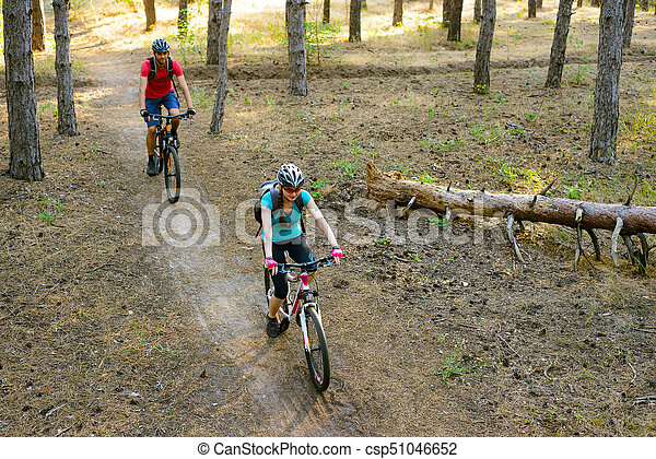 Young Couple Riding the Mountain Bikes in the Pine Forest. Adventure and Family Travel Concept. - csp51046652