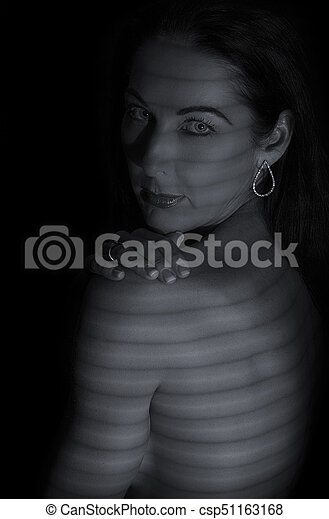 Portrait of a woman posing in darkness with shadow lines of blinds artistic conversion - csp51163168