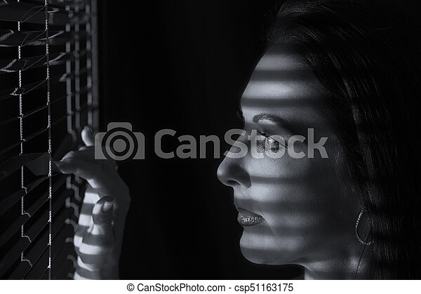 Portrait of a woman standing in darkness looking through blinds artistic conversion - csp51163175