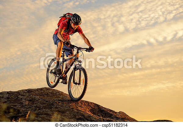 Cyclist in Red Riding the Bike Down the Rock at Sunset. Extreme Sport and Enduro Biking Concept. - csp51182314