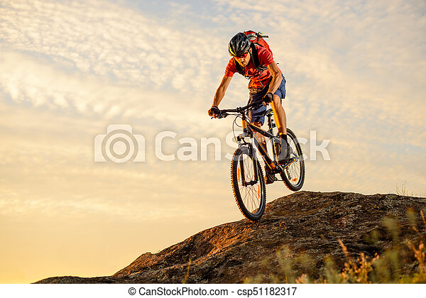 Cyclist in Red Riding the Bike Down the Rock at Sunset. Extreme Sport and Enduro Biking Concept. - csp51182317