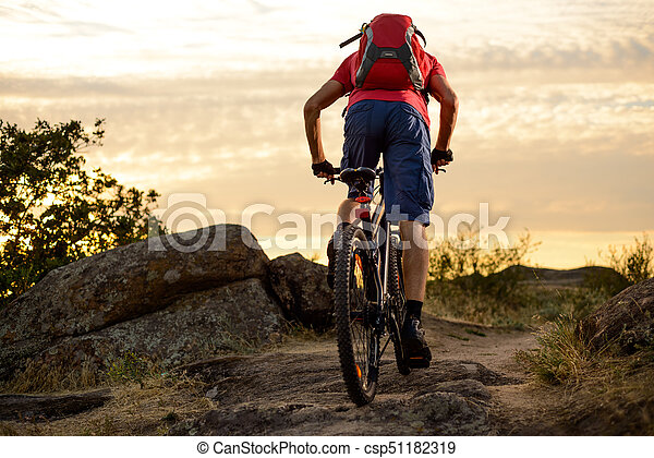 Cyclist in Red Riding the Bike on the Rocky Trail at Sunset. Extreme Sport and Enduro Biking Concept. - csp51182319