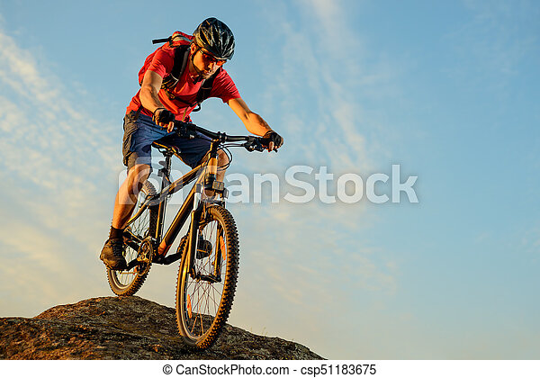 Cyclist in Red Riding the Bike Down the Rock on the Blue Sky Background. Extreme Sport and Enduro Biking Concept. - csp51183675