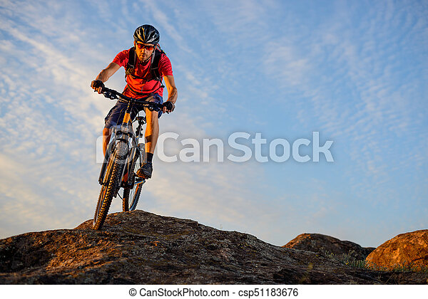 Cyclist in Red Riding the Bike Down the Rock on the Blue Sky Background. Extreme Sport and Enduro Biking Concept. - csp51183676