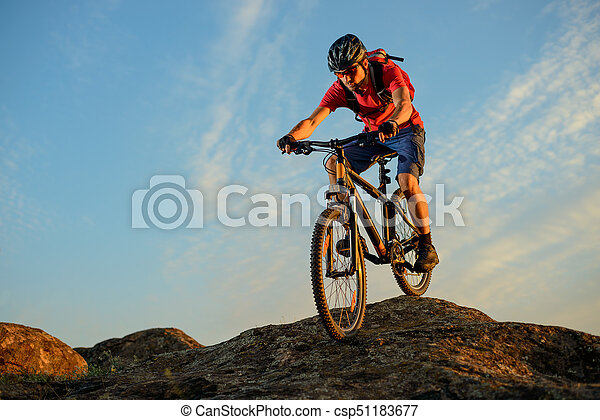 Cyclist in Red Riding the Bike Down the Rock on the Blue Sky Background. Extreme Sport and Enduro Biking Concept. - csp51183677