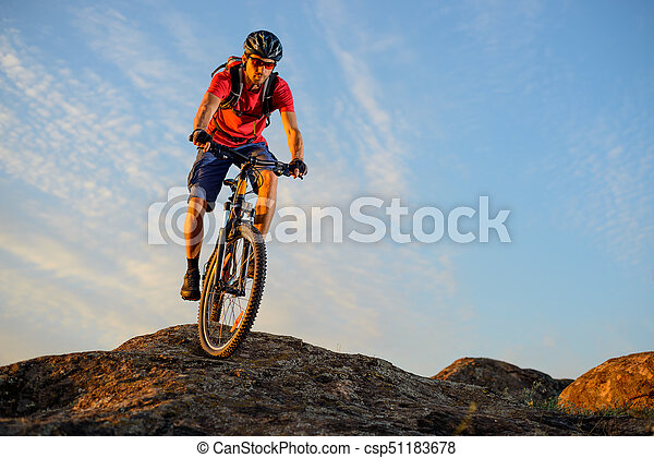 Cyclist in Red Riding the Bike Down the Rock on the Blue Sky Background. Extreme Sport and Enduro Biking Concept. - csp51183678