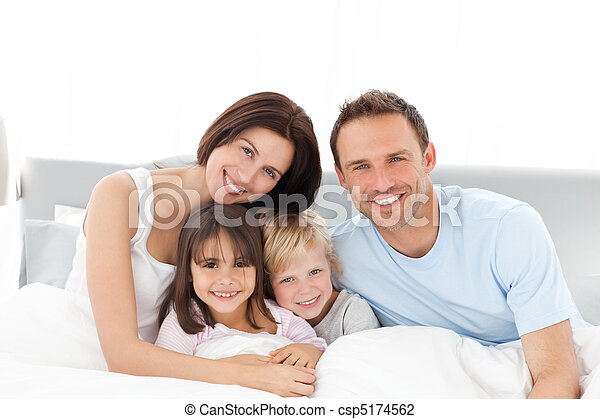 Portrait of a happy family sitting on the bed - csp5174562
