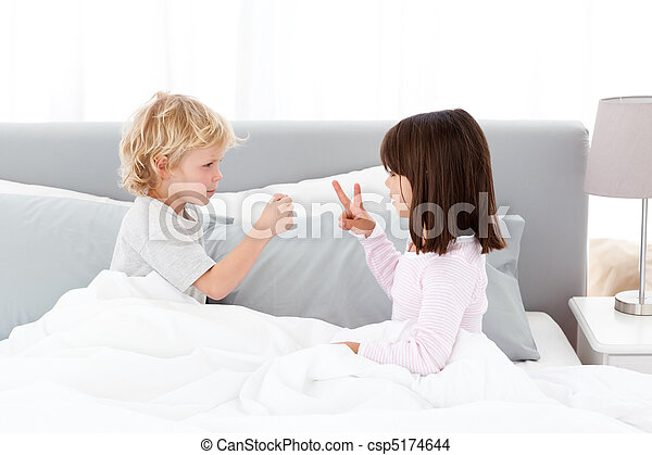 Cute brother and sister playing rock paper and scissors  - csp5174644