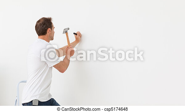 Rear view of a man hammering against a white wall - csp5174648