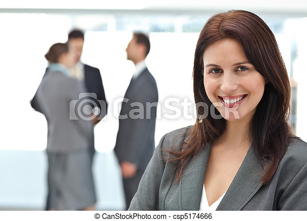 Happy businesswoman posing while her team discussing - csp5174666