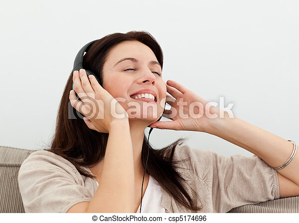 Happy woman enjoying a song on the sofa - csp5174696