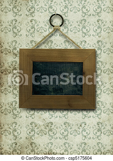 empty wooden frame fixed on a old and dirty wall, the inner part of the frame is a slate, the wallpaper is stained and dirty with arabesques on it, the frame is fixed by a nail ans a rope - csp5175604