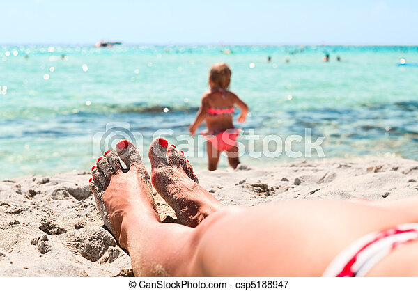 Legs of beautiful young unrecognizable girl lying on sand in beach near a sea and little playing child - csp5188947