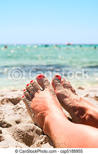 Legs of beautiful young unrecognizable girl lying on a sand in beach near a sea - csp5188955