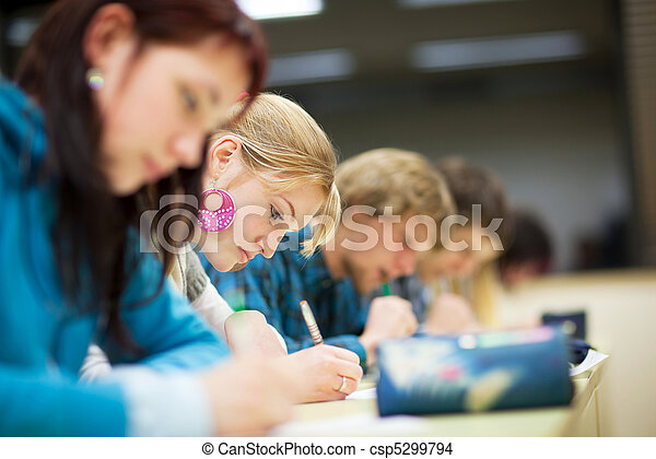pretty female college student sitting an exam in a classroom full of students (shallow DOF; color toned image)