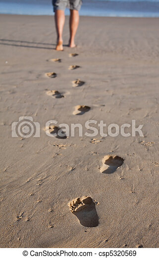 Footprints in wet sand in a line with a man walking to the sea - csp5320569