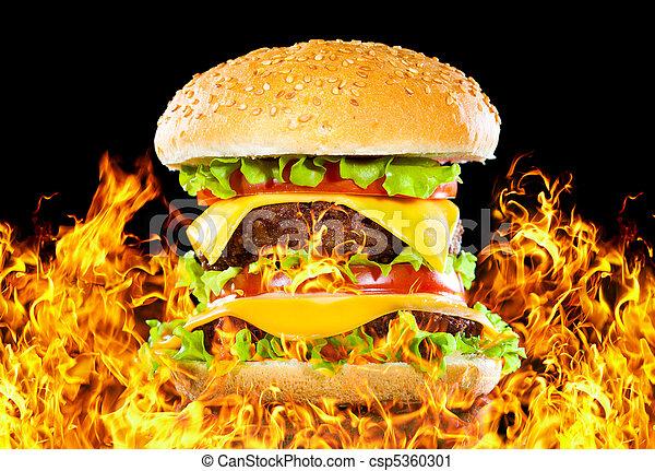 Tasty hamburger on fire on a dark - csp5360301