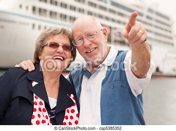 Senior Couple On Shore in Front of Cruise Ship - csp5385352