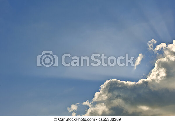 Beautiful inspirational image of sun rays bursting through clouds against vibrant blue sky - csp5388389