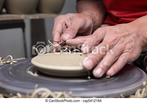 Potter\'s hands finishing clay plate