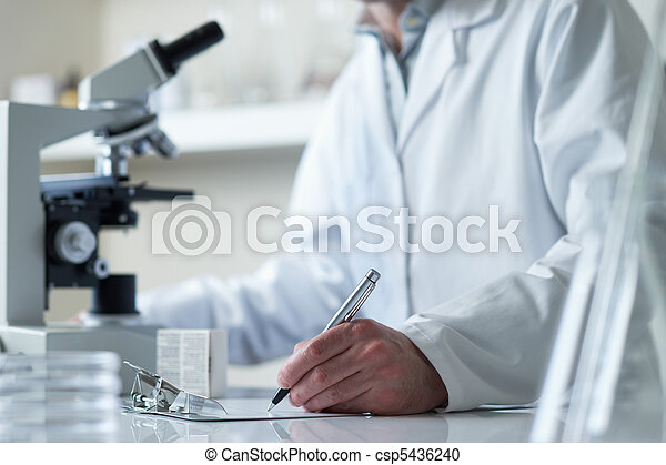 scientist conducting research with microscope  - csp5436240