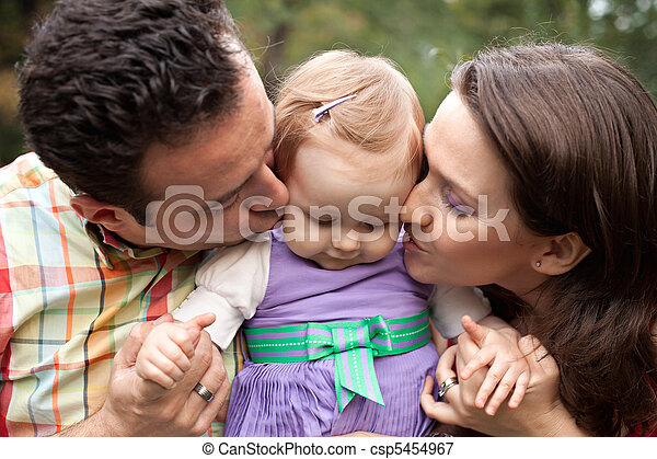 Kiss of love - parents with their baby girl - csp5454967