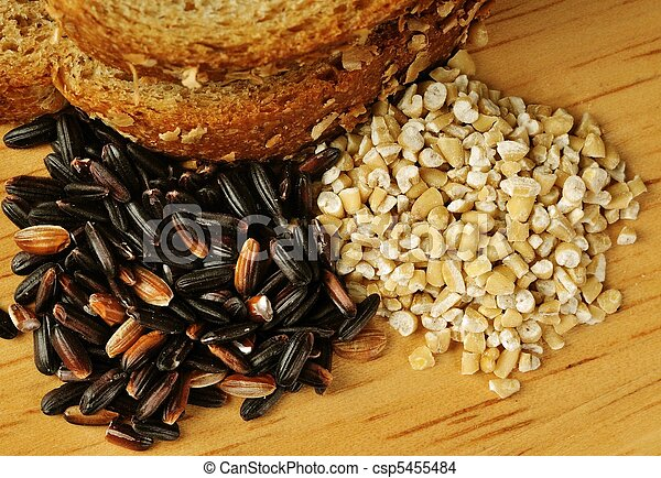 Close up image of whole wheat bread, steel cut oats, and black rice on wood cutting board. - csp5455484