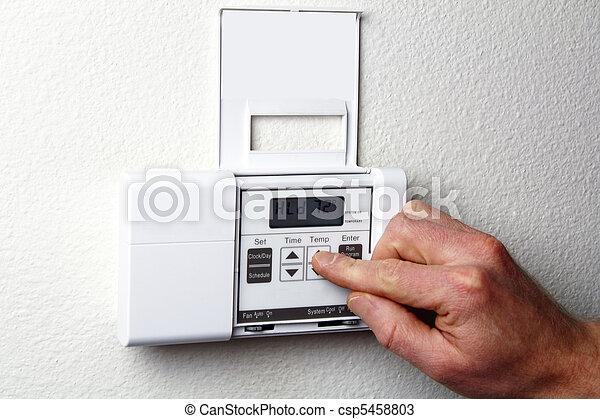 Hand on Thermostat - csp5458803