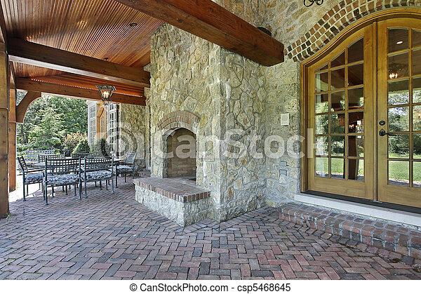 Brick patio with stone fireplace - csp5468645