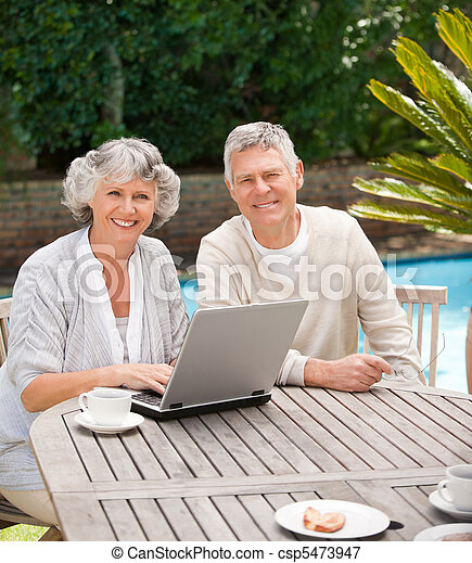 Retired couple working on their laptop - csp5473947