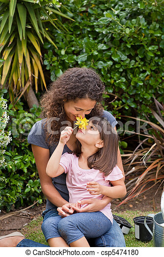 Mother smelling a flower with her daughter - csp5474180