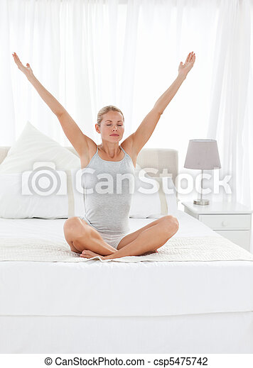 Beautiful woman practicing yoga on her bed  - csp5475742