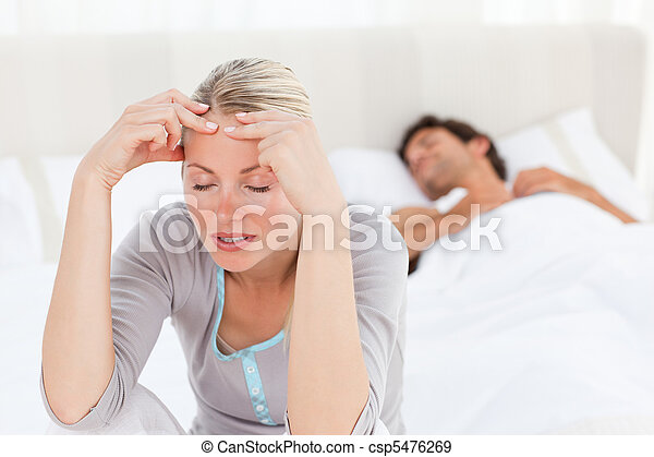 Attractive woman having a headache while her husband is sleeping at home - csp5476269