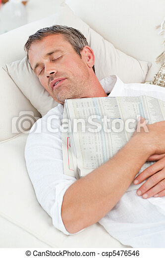 Exhausted man sleeping on the couch at home - csp5476546