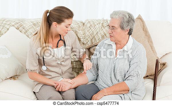 Beautiful nurse taking the pulse - csp5477774