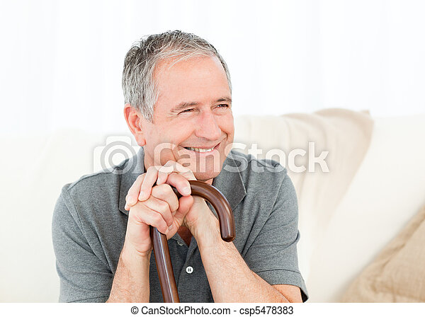 Mature man with his walking stick on his bed at home - csp5478383